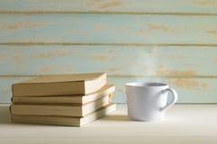 与书的热的咖啡在白色桌上 免版税库存图片