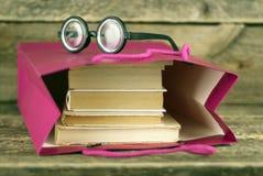 与书的纸袋在木背景和玻璃 库存照片