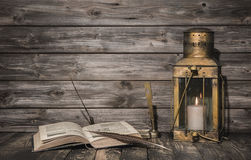 与书的老葡萄酒背景和羽毛和一土气lanter 免版税库存照片