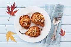 与乳清干酪、核桃、蜂蜜和桂香的被烘烤的梨在一张蓝色葡萄酒桌上的板材从上面 可口秋天点心 免版税库存图片