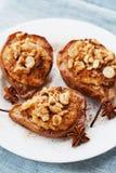 与乳清干酪、核桃、蜂蜜和桂香的被烘烤的梨在蓝色布料背景的一块白色板材 可口秋天点心 免版税库存照片
