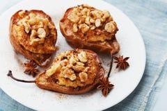 与乳清干酪、核桃、蜂蜜和桂香的被烘烤的梨在蓝色背景的一块白色板材 可口秋天点心 免版税库存照片