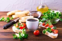 与乳清干酪、菜用结页草和西红柿的Bruschetta 咖啡 库存照片