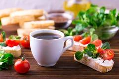 与乳清干酪、菜用结页草和西红柿的Bruschetta 咖啡 图库摄影