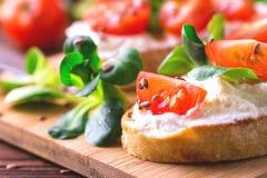 与乳清干酪、菠菜、菜用结页草和西红柿的Bruschetta 库存照片