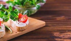 与乳清干酪、菠菜、菜用结页草和西红柿的Bruschetta 免版税库存照片