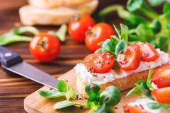 与乳清干酪、菠菜、菜用结页草和西红柿的Bruschetta 库存图片