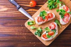 与乳清干酪、菠菜、菜用结页草和西红柿的Bruschetta 免版税图库摄影