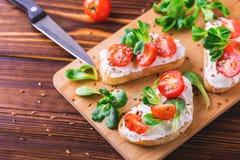 与乳清干酪、菠菜、菜用结页草和西红柿的Bruschetta 免版税库存图片