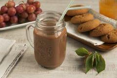 与乳白玻璃的巧克力牛奶可可粉木表面上 免版税库存图片