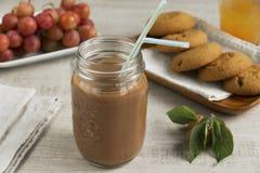 与乳白玻璃的巧克力牛奶可可粉木表面上 免版税库存照片