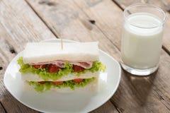 与乳白玻璃的火腿和乳酪三明治 库存图片