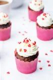 与乳脂干酪结霜和心脏的杯形蛋糕为Valen洒 免版税图库摄影