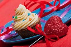 与乳脂状的奶油的巧克力蛋糕在一块蓝色板材,以巧克力题字爱 库存照片