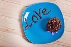 与乳脂状的奶油的巧克力蛋糕在一块蓝色板材,以巧克力题字爱 库存图片