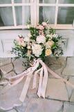 与乳脂状的玫瑰、白色康乃馨和南北美洲香草立场的土气婚礼花束在地板上 特写镜头 图库摄影