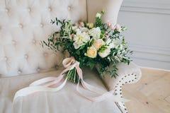 与乳脂状的玫瑰和白色康乃馨的土气婚礼花束在豪华奶油色沙发 特写镜头 侧视图 免版税图库摄影