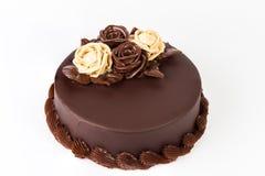 与乳脂状的玫瑰装饰的巧克力蛋糕在上面 免版税库存照片