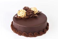 与乳脂状的玫瑰装饰的巧克力蛋糕在上面 库存图片