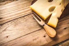 与乳酪叉子的Maasdam乳酪在年迈的木背景,选择聚焦的一个黑暗的切板 免版税库存照片