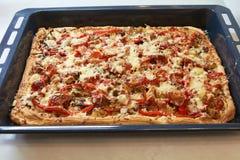 与乳酪和蕃茄顶部的西西里人的长方形薄饼在烤板 库存照片