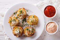 与乳酪和调味汁特写镜头的切的被烘烤的土豆 水平的t 库存照片
