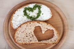 与乳酪奶油传播的面包和心脏由在板材的草本制成 库存照片