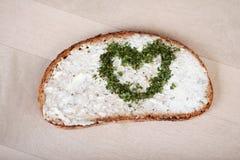 与乳酪奶油传播的面包和心脏由草本制成 库存图片