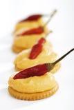 与乳酪奶油的薄脆饼干,装饰用红色意大利辣味香肠 库存照片