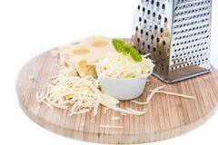 与乳酪磨丝器的Emmentaler在白色 库存照片