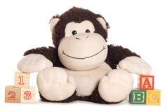 与了解块的软的玩具猴子 免版税库存图片