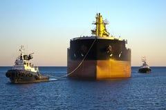 与二条猛拉小船协助的货船 免版税库存照片