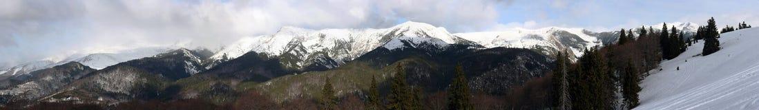 与云彩全景的多雪的山峰 图库摄影