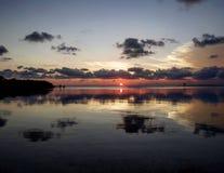 与云彩反射的桃红色海岛日落 免版税库存照片