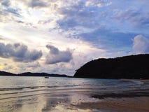 与云彩反射的海滨在晚上 库存照片