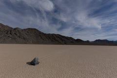 与云彩和山遮暗的天空的航行石头 免版税库存照片