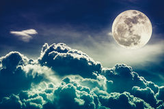与云彩和明亮的满月的夜间天空与发光 阴级射线示波器 免版税图库摄影