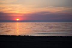 与云彩和波浪的海日出 库存图片