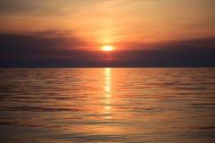 与云彩和波浪的海日出 图库摄影