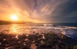 与云彩和海波浪的日落 图库摄影