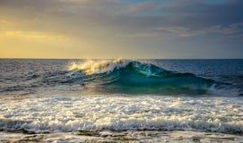 与云彩和海波浪的日落 免版税库存照片