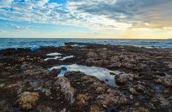 与云彩和海的日落在火山的海岸,克利特,希腊挥动 库存照片