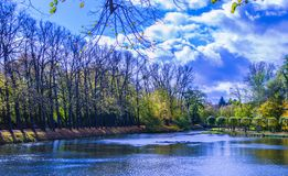 与云彩和湖的五颜六色的艺术性的公园风景 库存图片