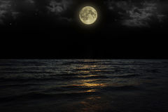 与云彩和满月的美丽的不可思议的蓝色夜空在水中担任主角反射 免版税库存图片