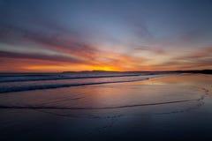 与云彩波浪橙色太阳天空的海滩 免版税图库摄影
