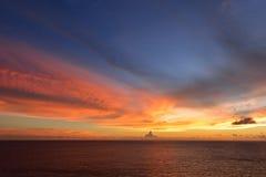 与云彩爆炸的日落天空和在海洋的金黄光,长期 库存图片