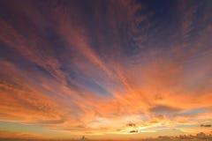 与云彩爆炸的日落天空和在海洋的金黄光,长期 图库摄影