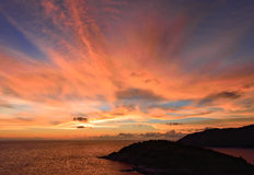 与云彩爆炸的日落天空和在海洋的金黄光,长期 免版税库存照片