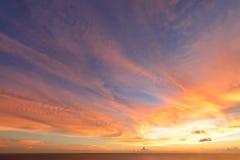 与云彩爆炸的日落天空和在海洋的金黄光,长期 库存照片