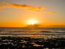 与云彩的五颜六色的日落由海洋 图库摄影